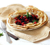 Pancakes with fresh berries and mint. Plate with fresh berries and pancakes filled with homemade jam placed over a napkin Royalty Free Stock Photography
