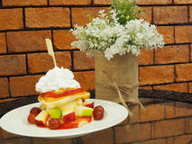 Pancakes with fresh fruits and whipped cream, and decorated arti Royalty Free Stock Photos