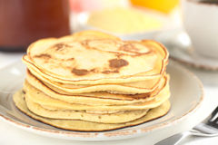Pancakes. Fresh homemade pancakes with coffee, butter and maple syrup in the back (Selective Focus, Focus on the front of the upper three pancakes Stock Photos