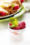 Pancakes with fresh raspberry. Pancake rolls with fresh raspberry and mint, selcetive focus Stock Photo
