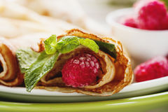 Pancakes with fresh raspberry. Pancake rolls with fresh raspberry and mint, selcetive focus closeup Royalty Free Stock Photo