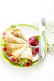 Pancakes with fresh raspberry. Pancake rolls with fresh raspberry and mint, selcetive focus top view Royalty Free Stock Photos