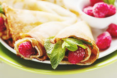 Pancakes with fresh raspberry. Pancake rolls with fresh raspberry and mint, selective focus closeup Royalty Free Stock Photo