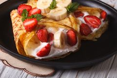 Pancakes with fresh strawberries, bananas and cream close-up Stock Images