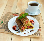 Pancakes with fresh strawberries, chocolate, decorating mint leaves and a cup of tea on a light wooden background Royalty Free Stock Photos