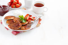 Pancakes with fresh strawberries, jam and tea for breakfast Royalty Free Stock Photo