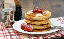 Pancakes with fresh strawberries, powdered sugar and maple syrup Stock Photography