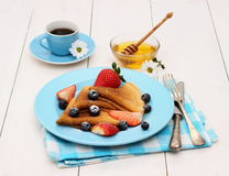 Pancakes with fresh strawberry, blueberry, coffee and honey Stock Photo