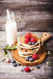 Pancakes with fresh summer berries and bottle of milk Stock Photo