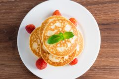 Pancakes fritters with strawberries on a plate. royalty free stock photo
