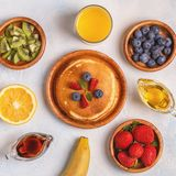 Pancakes with fruit, honey, maple syrup. Top view royalty free stock photography
