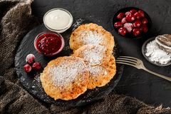 Pancakes with fruit jam, cherries, sour cream and icing sugar on black slate over dark background. Traditional Russian cuisine at the Pancake week or royalty free stock images