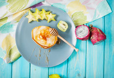 Pancakes with fruits on blue wood plate. Royalty Free Stock Photo