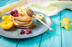 Pancakes with fruits on blue wood plate Royalty Free Stock Image