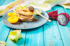 Pancakes with fruits on blue wood plate Royalty Free Stock Photography