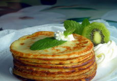 Pancakes with fruits, cream and mint. Homemade meal cooked tasty and decorated with fruits Royalty Free Stock Photo