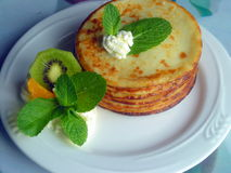 Pancakes with fruits, cream and mint. Homemade meal cooked tasty and decorated with fruits Stock Photos
