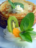 Pancakes with fruits, cream and mint. Homemade meal cooked tasty and decorated with fruits Stock Photo