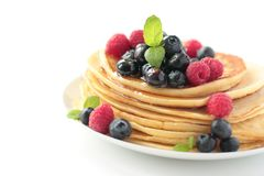 Pancakes with fruits and honey. Pancake with fresh blueberry and raspberry with mint leafs Royalty Free Stock Images