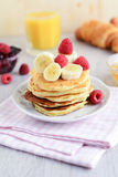 Pancakes with fruits, juice and croissant: breakfat table Stock Image