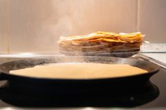 Pancakes fry in a pan. the process of cooking pancakes on an electric stove royalty free stock photography