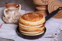 Pancakes in a frying pan. On the desk Royalty Free Stock Photos