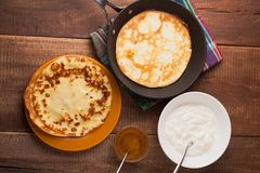 Pancakes on a frying pan with sour cream and honey. Homemade pancakes on a frying pan with sour cream and honey on wood table Stock Photography