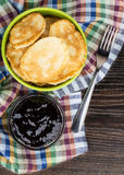 Pancakes in green bowl, jam and fork on checkered towel Stock Photos