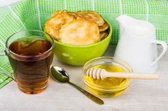 Pancakes in green bowl, jug milk, honey, teaspoon and tea Royalty Free Stock Photography