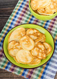 Pancakes in green plate and bowl on checkered towel. On wooden table Royalty Free Stock Photo