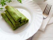 Pancakes. Green pancakes on white plate Stock Photo