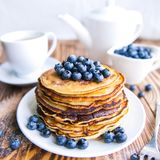 Pancakes healthy breakfast with blueberries, bog whortleberry, cup of green tea, cup of blueberries and teapot. On brown wooden background Stock Photography