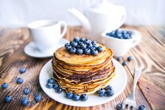 Pancakes healthy breakfast with blueberries, bog whortleberry, cup of green tea, cup of blueberries and teapot. On brown wooden background Royalty Free Stock Photography