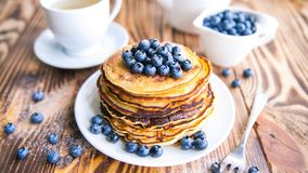 Pancakes healthy breakfast with blueberries, bog whortleberry, cup of green tea, cup of blueberries and teapot. On brown wooden background Royalty Free Stock Photo