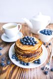 Pancakes healthy breakfast with blueberries, bog whortleberry, cup of green tea, cup of blueberries and teapot. On brown wooden background Royalty Free Stock Photos