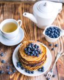 Pancakes healthy breakfast with blueberries, bog whortleberry, cup of green tea, cup of blueberries and teapot. On brown wooden background Royalty Free Stock Image
