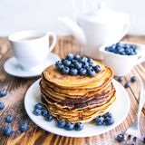 Pancakes healthy breakfast with blueberries, bog whortleberry, cup of green tea, cup of blueberries and teapot. On brown wooden background Stock Photo