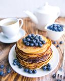 Pancakes healthy breakfast with blueberries, bog whortleberry, cup of green tea, cup of blueberries and teapot. On brown wooden background Stock Images
