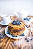 Pancakes healthy breakfast with blueberries, bog whortleberry, cup of green tea, cup of blueberries and teapot. On brown wooden background Stock Photos