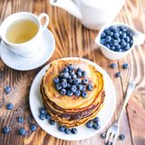 Pancakes healthy breakfast with blueberries, bog whortleberry, cup of green tea, cup of blueberries and teapot. On brown wooden background Stock Image