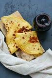 Pancakes. Homemade pancakes   in  cast- iron pan  and blueberries jam  on   black slate Stock Photos