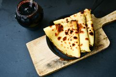 Pancakes. Homemade pancake crepe     in cast-iron pan on black background Stock Photo