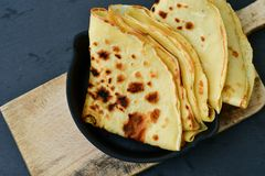 Pancakes. Homemade pancake crepe     in cast-iron pan on black background Royalty Free Stock Photography