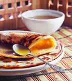 Pancakes and  honey. Thin pancake and some sweet honey Stock Image