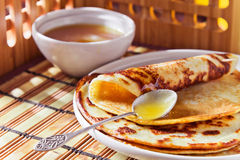 Pancakes and  honey. Thin pancake and some sweet honey Royalty Free Stock Images