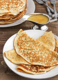 Pancakes with honey. On the white plate royalty free stock photography