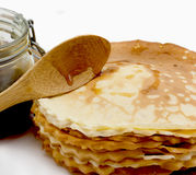Pancakes with honey. Pancakes, wooden spoon and  glass jar with honey isolated on a white background Royalty Free Stock Photos