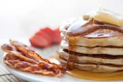 Pancakes with honey, bacon and strawberries. Pancakes with butter and honey served with bacon and strawberries Stock Image