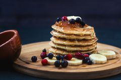 Pancakes with honey, bananas, jam and berrieson a wooden plate Menu , restaurant recipe concept. Served in royalty free stock images