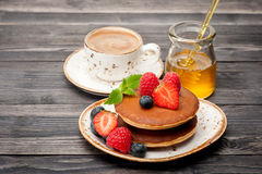 Pancakes, honey, berries and a cup of coffee espresso Royalty Free Stock Image